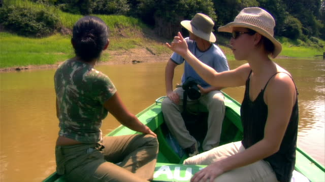 wide shot tour guide pointing and talking to couple on small boat going up river/ the amazon, brazil - guidance stock videos & royalty-free footage