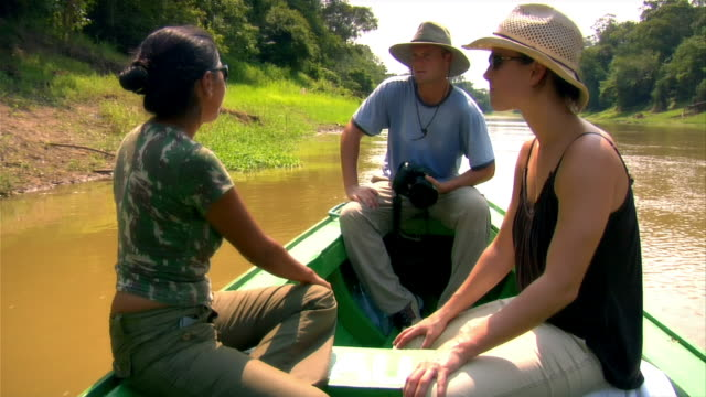 wide shot tour guide talking to couple on small boat going up river/ the amazon, brazil - paar mittleren alters stock-videos und b-roll-filmmaterial