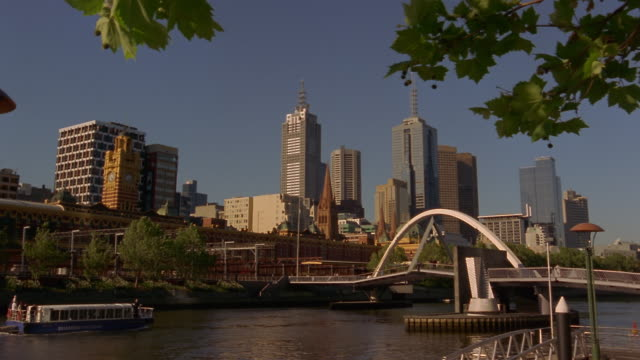 wide shot tourboat passing under southbank footbridge/ melbourne, australia - tourboat stock videos & royalty-free footage