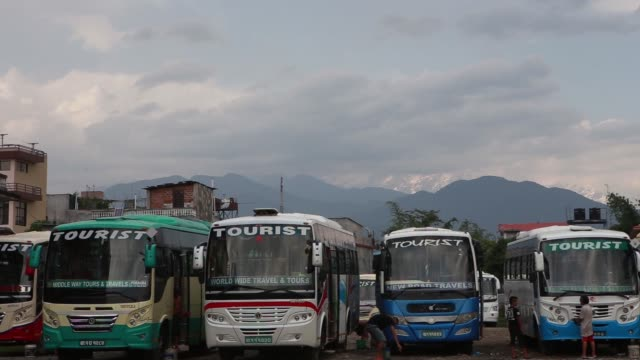 Wide shot Tourist buses prepare to leave for Pokhara from Kathmandu Wide shot Tourist buses sit parked in a lot in Pokhara Nepal Wide shot A man...