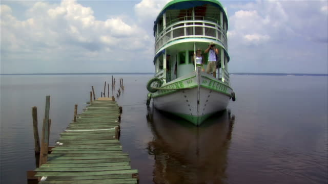 stockvideo's en b-roll-footage met wide shot tourist couple riding ferry boat leaving dock / man taking photos / rio negro, brazil - color negro
