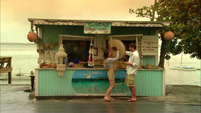 wide shot tourist couple shopping at roadside gift shop/ harbor island, bahamas - souvenir stock videos and b-roll footage
