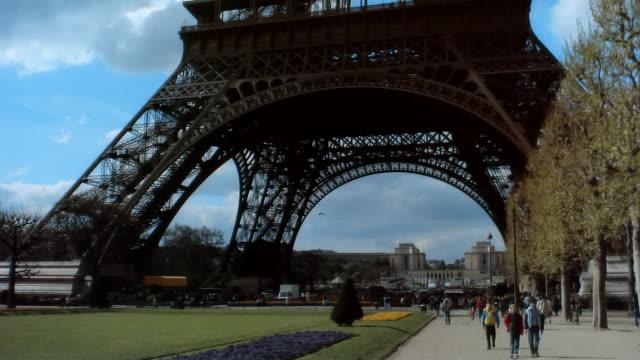 wide shot tourists walking below eiffel tower/ paris, france - eiffel tower stock videos & royalty-free footage