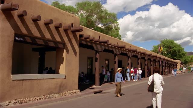 wide shot tourists walking outside the palace of the governors museum / santa fe, new mexico - adobe bildbanksvideor och videomaterial från bakom kulisserna