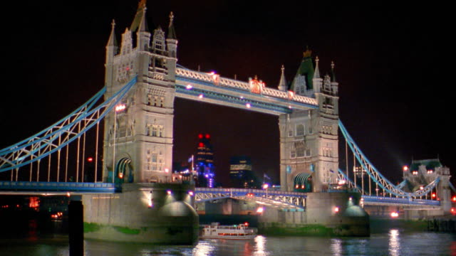Wide shot Tower Bridge and Thames River with boat at night / London