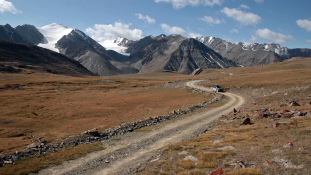 stockvideo's en b-roll-footage met wide shot toyota 4runner with rooftop box driving on dirt road across vast valley with glacier snow capped majestic mountains in distance. - toyota motor