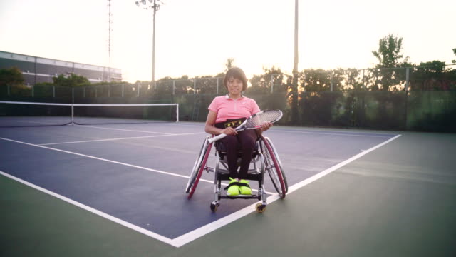 Wide shot tracking in to a mid portrait of an adaptive tennis player
