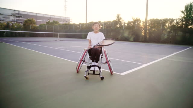 wide shot tracking in to a mid portrait of an adaptive tennis player - sportsperson stock videos & royalty-free footage