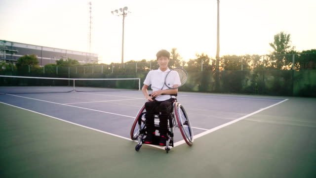 wide shot tracking in to a mid portrait of an adaptive tennis player - sporting term stock videos & royalty-free footage