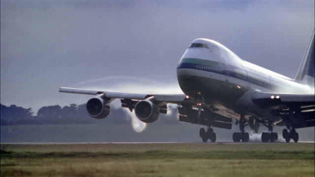Wide shot tracking shot Air New Zealand Boeing 747 touching down with condensation on wings at AKL airport/ New Zealand