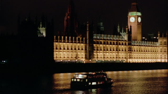 Wide shot tracking shot barge sailing past Houses of Parliament on River Thames at night / London