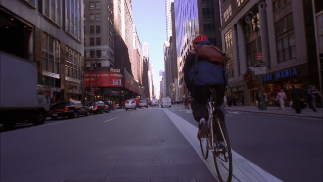 stockvideo's en b-roll-footage met wide shot tracking shot bike messenger riding down madison avenue / nyc - rijwiel