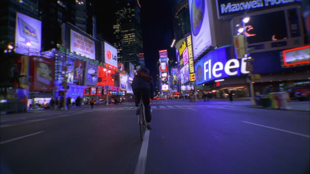vídeos de stock e filmes b-roll de wide shot tracking shot bike messenger riding through times square at night / nyc - ciclismo