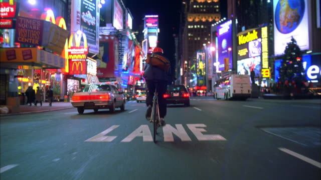 Wide shot tracking shot bike messenger riding through Times square at night / NYC