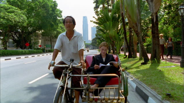 Wide shot tracking shot businesswoman riding in tricycle rickshaw, reading document and looking around / Singapore