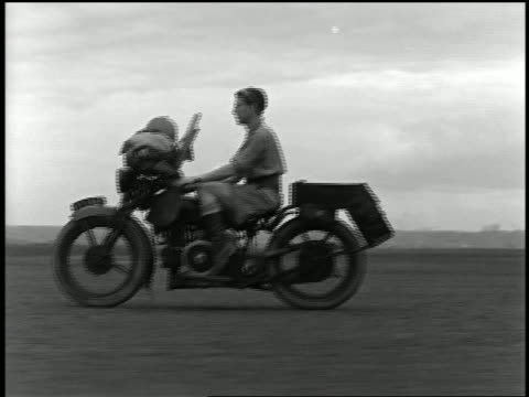 1932 wide shot tracking shot explorer riding motorcycle across desert / airplane in background - 1932 stock-videos und b-roll-filmmaterial