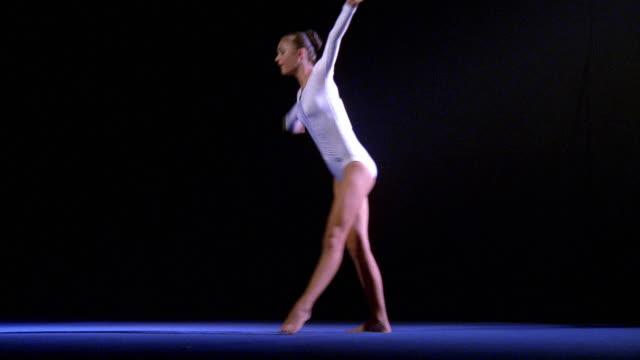wide shot tracking shot female gymnast peforming floor exercise - cartwheel stock videos & royalty-free footage