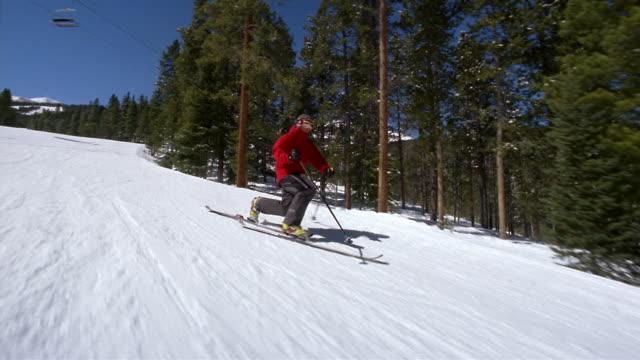 vídeos de stock, filmes e b-roll de wide shot tracking shot freestyle skier doing lunges down slope - roupa de esqui
