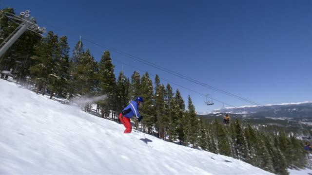 wide shot tracking shot freestyle skier skiing down moguls / passing skiers riding chairlift - freestyleskidåkning bildbanksvideor och videomaterial från bakom kulisserna