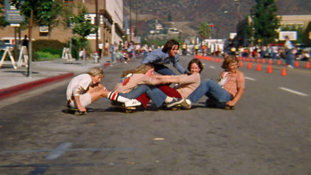 vídeos de stock e filmes b-roll de wide shot tracking shot group of young people sitting and standing on skateboards / linking boards with bodies / turning - 1976