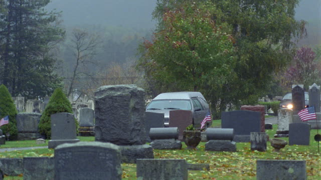 wide shot tracking shot hearse driving on road in cemetery / vermont - funeral procession stock videos & royalty-free footage