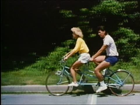 1987 wide shot tracking shot man and woman riding tandem bicycle against verdant background