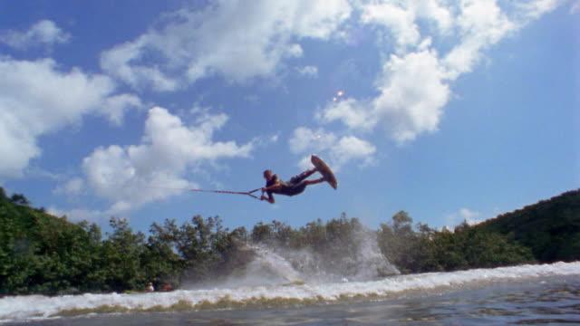 wide shot tracking shot man on wakeboard jumping in air and landing on water / kauai, hawaii - ウェイクボーディング点の映像素材/bロール