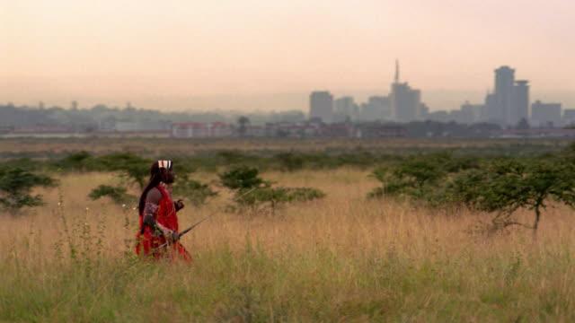 vídeos de stock, filmes e b-roll de wide shot tracking shot masai tribesman walking across plain with nairobi in background / kenya - tempo real