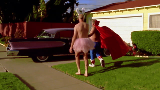 wide shot tracking shot mature men in superhero and ballerina costumes walking from front yard to car - ballettröckchen stock-videos und b-roll-filmmaterial