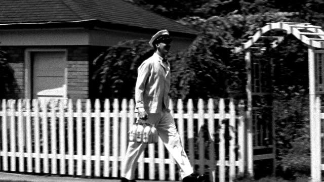 stockvideo's en b-roll-footage met wide shot tracking shot reenactment milkman walking on street and carrying bottles - tuinhek