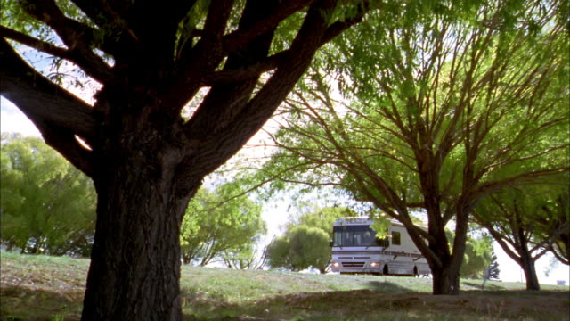 wide shot tracking shot rv driving past trees w/blue sky in background - camper van stock videos and b-roll footage
