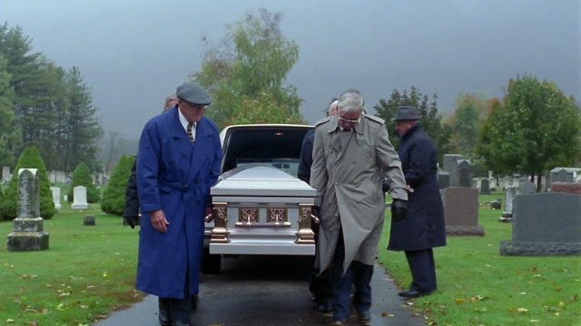 wide shot tracking shot senior men removing coffin from hearse and carrying it to grave / vermont - 棺点の映像素材/bロール