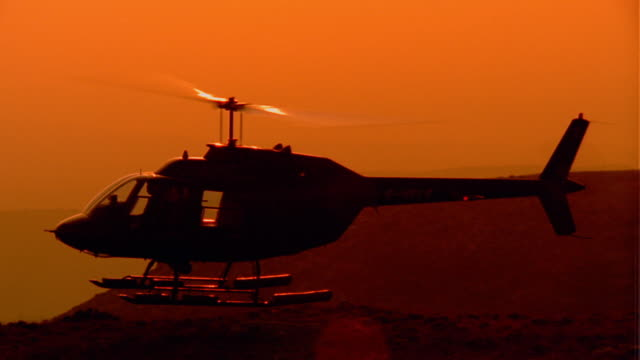 wide shot tracking shot silhouette slow motion helicopter taking off from hillside with sun in background / provence, france - helicopter stock videos & royalty-free footage