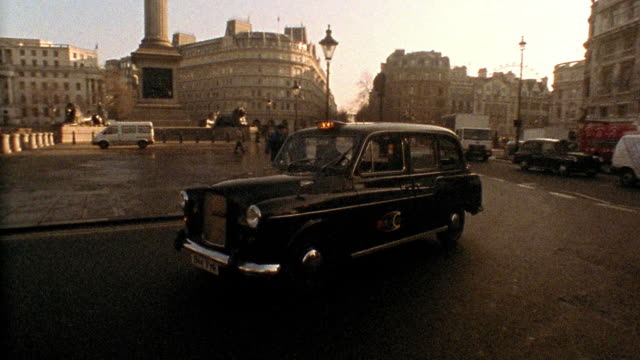 Wide shot tracking shot slow motion taxi around Trafalgar Square with Nelson's Column and National Gallery in background / London