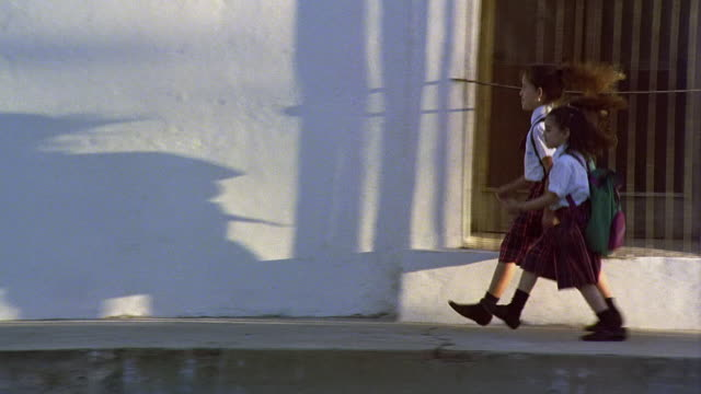 Wide shot tracking shot two young girls in school uniforms skipping on sidewalk