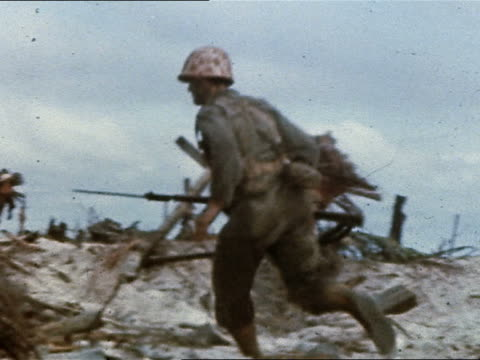 wide shot tracking shot us marines advancing up shell-torn beach / philippines - guerra del pacifico video stock e b–roll
