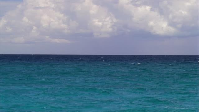 wide shot tracking shot waves rolling on ocean / nassau, bahamas - nassau stock videos & royalty-free footage