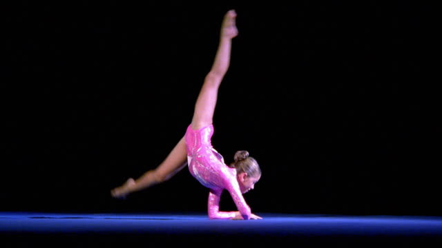 Wide shot tracking shot young female gymnast peforming floor exercise