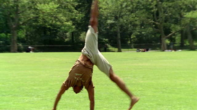 stockvideo's en b-roll-footage met wide shot tracking shot young man doing cartwheels across lawn in central park / new york city - acrobatiek