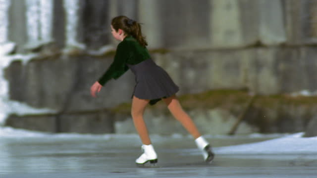 vidéos et rushes de wide shot tracking shot young teenage girl ice skating on frozen lake / vermont - patinage sur glace
