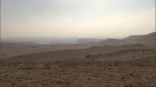 Wide Shot, tracking-left - The Great Pyramids tower above the Giza Plateau / Egypt