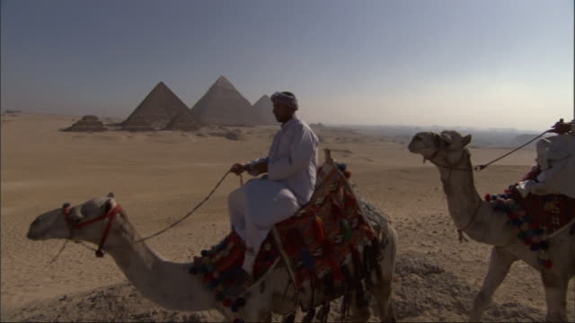 Wide Shot, tracking-left - Three men ride camels near the Great Pyramids in Egypt