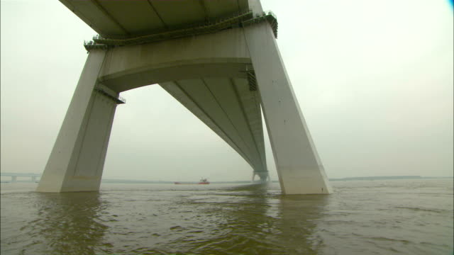 wide shot tracking-left - water ripples beneath the yangtze river bridge./nanjing, china - nanjing stock videos & royalty-free footage