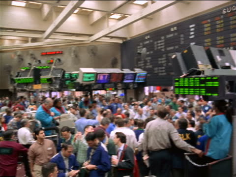 wide shot PAN traders beneath electronic displays on exchange floor / Coffee, Sugar + Cocoa Exchange, NYC