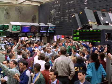 vidéos et rushes de wide shot traders making hand signals on exchange floor / coffee, sugar + cocoa exchange, nyc - 1990 1999