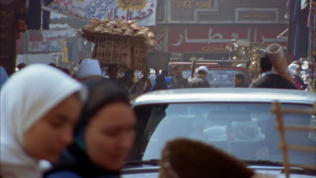 wide shot traffic and people carrying goods in street bazaar in old section / cairo, egypt - egypt stock videos & royalty-free footage