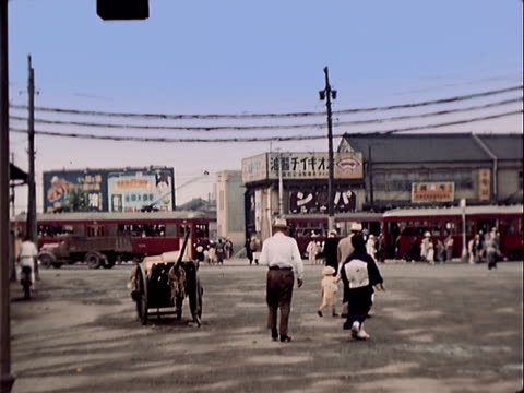 vídeos de stock, filmes e b-roll de 1939 wide shot traffic and people moving through busy intersection/ japan - 1930 1939
