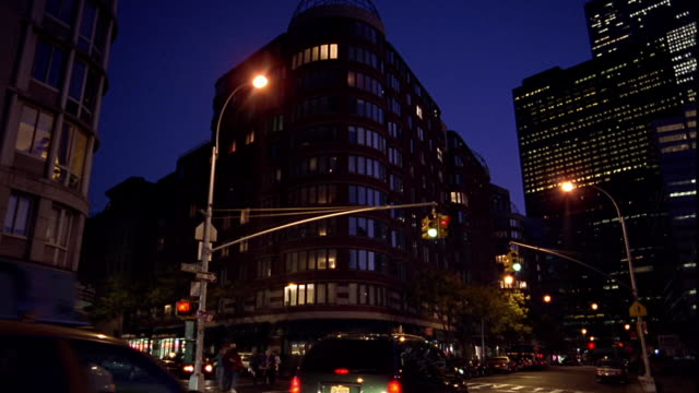 wide shot traffic at intersection in front of apartment building on greenwich street at night / tribeca, new york city - tribeca stock videos & royalty-free footage