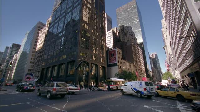 vídeos de stock e filmes b-roll de wide shot traffic at the corner of 57th street and park avenue / tilt up skyscrapers / new york city - ano 2000