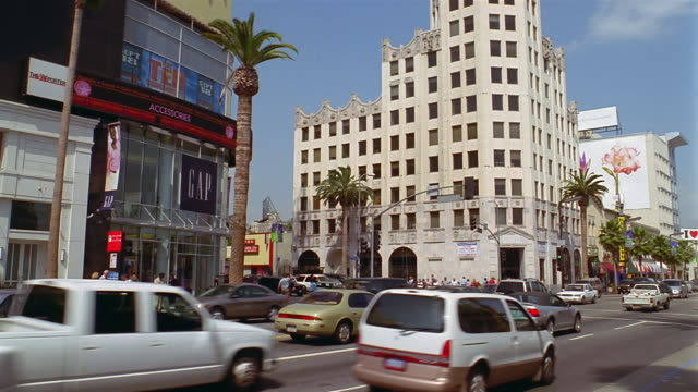Wide shot traffic at the corner of Hollywood Boulevard and Highland Avenue / Los Angeles